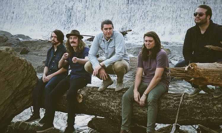 Swim in the Wild band members sitting on a log in front of a waterfall.