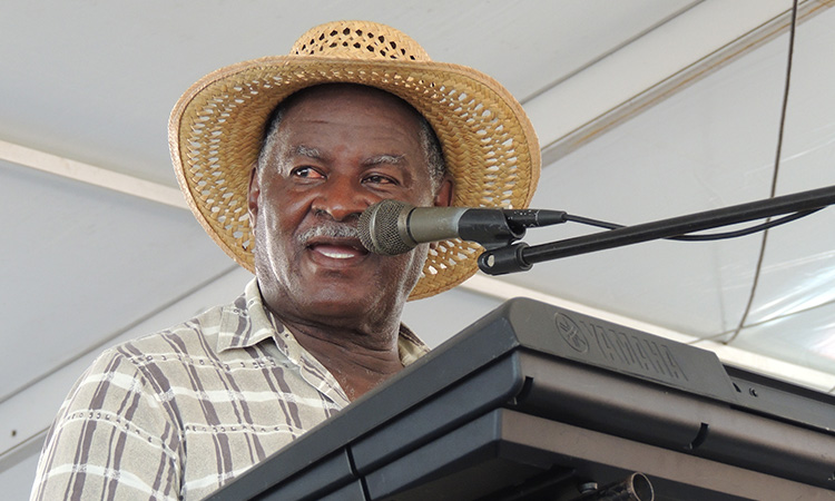 A musician in a straw hat singing into a microphone in front of a keyboard.