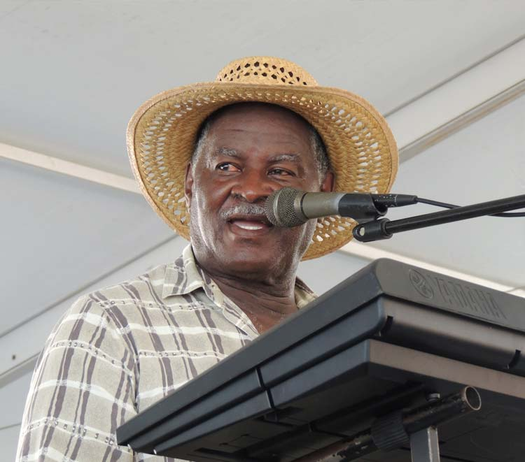 A one man band musician in a straw hat sings into microphone while playing a keyboard.