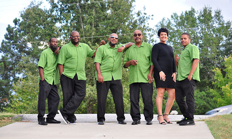 Six band members, five men and one women standing in a line in a wooded outdoor setting and leaning on one another. All the men wear lime green shirts and black pants. The woman wears a black dress and heels.