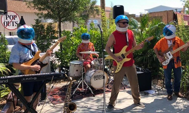 A band of four playing electric guitars, keyboard and drums on an outdoor stage, all wearing fake astronaut helmets.