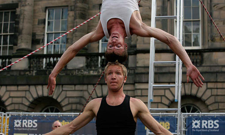 Two male performers outside in front of a building. One performer stands upright while the other balances upside down on the upright performer's head.