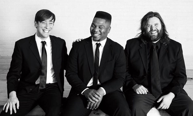 Black and white photo with three band members laughing with each other and wearing black tuxes. The band member farthest right is smiling directly at the camera.