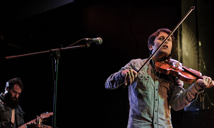 A young male musician playing the violin on stage next to a microphone and looking up and away with a young male guitarist in the background.