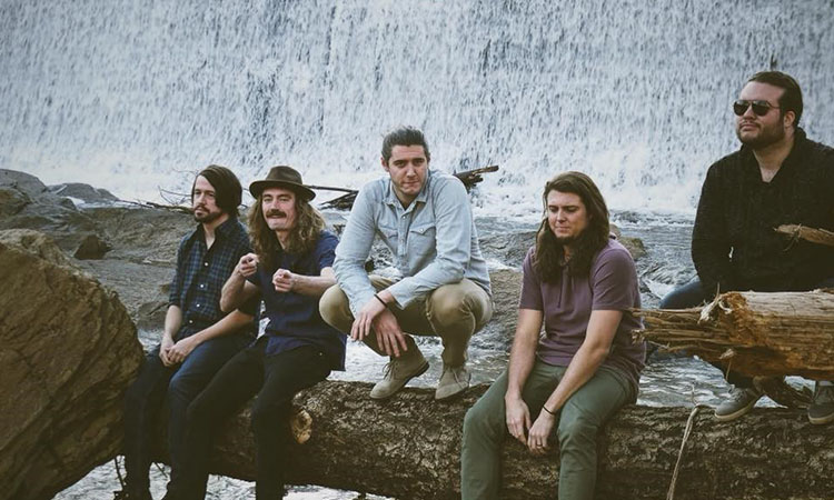 Five young male band members sitting on a fallen tree trunk in front of a waterfall and river. Three band members are looking away and two look at the camera. One points with both hands in the direction of the camera.
