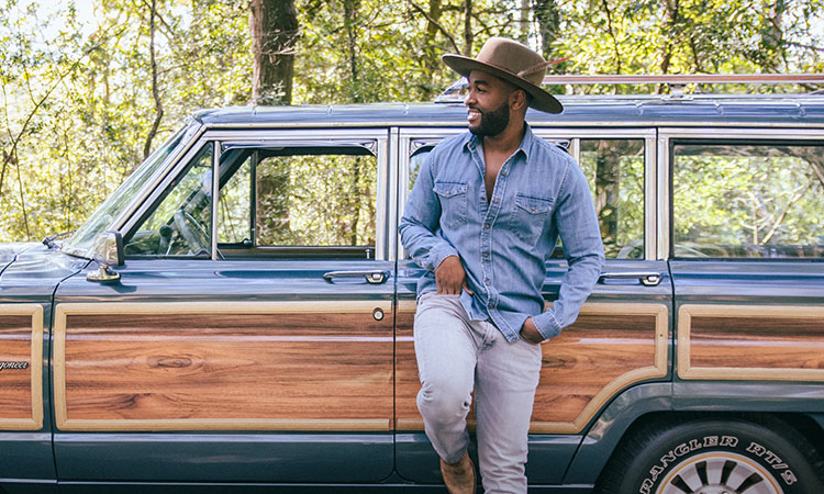 A young musician wearing a fedora with a feather in the band dressed in a denim shirt and jeans, looking off the to the left and leaning against a pristine blue Jeep Wrangler with wood panel sides.