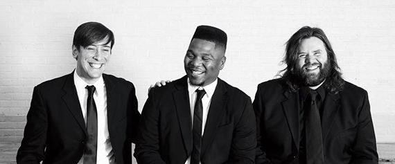 Black and white photo of three band members laughing together and wearing black tuxes. The band member farthest to the right is smiling directly at the camera.