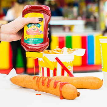 A hand squeezing ketchup over one of two corndogs with a bucket of fries against a colorful background.
