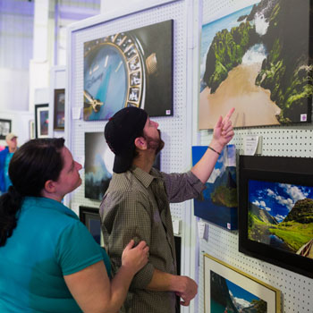 A man and a woman looking at artwork in a fair exhibition hall. The man is pointing to a landscape painting next to a closeup painting of a watch.