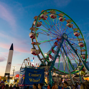 The fair ferris wheel lit up at dusk with the Midway attractions and the fair Rocket in the background.