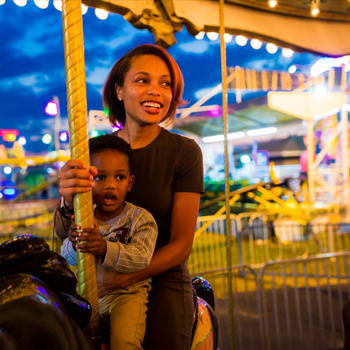 A mother and her young son riding on a carousel horse with fair lights in the background.
